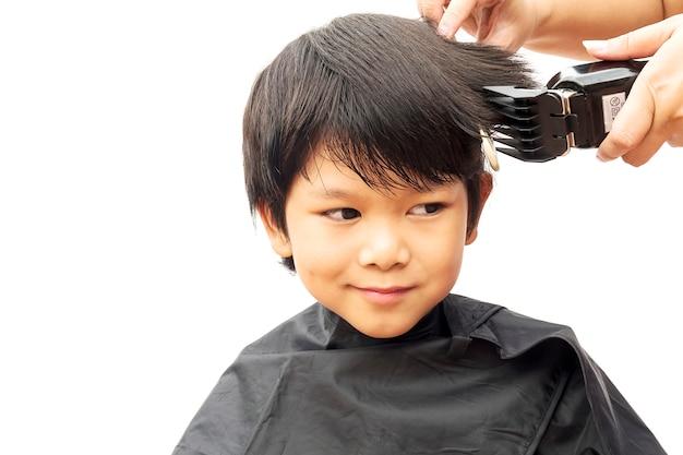 Ein junge wird sein haar durch den haaraufbereiter getrennt, der über weißem hintergrund lokalisiert wird