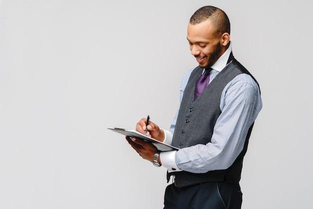 Ein junger afroamerikanermann, der einfache tischtafel und stift hält.