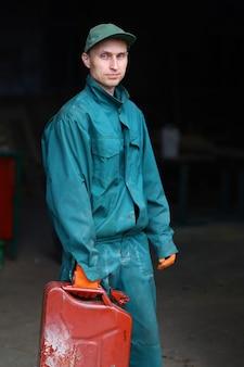Ein junger arbeiter in uniform hält einen kanister mit benzin in der hand