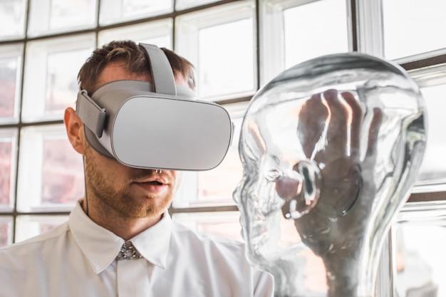 Ein junger arzt, der eine vr-brille trägt und eine schaufensterpuppe in der vr-simulation untersucht - zukünftiges technologiekonzept
