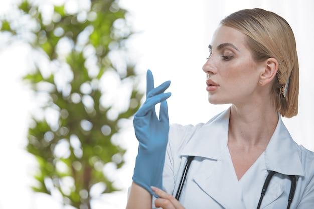 Ein junger arzt im büro mit einem stethoskop um den hals zieht sich einen blauen handschuh an