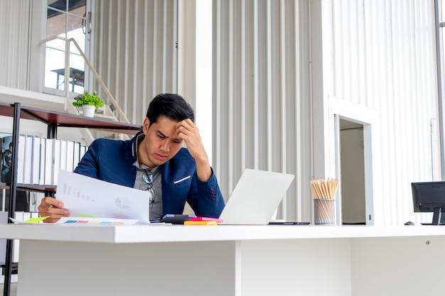 Ein junger asiatischer geschäftsmann betrachtet die schlechten finanziellen ergebnisse des unternehmens. sie fühlen sich enttäuscht