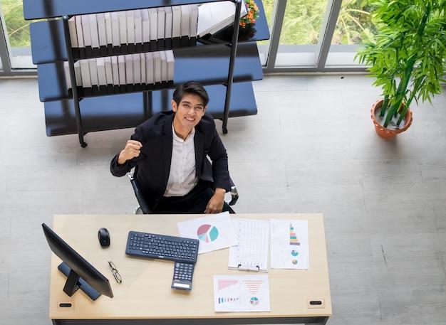 Ein junger asiatischer geschäftsmann, der auf einem stuhl in einer bequemen position im büro sitzt