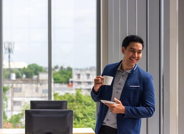 Ein junger asiatischer geschäftsmann trinkt kaffee im bürofenster in einem bequemen