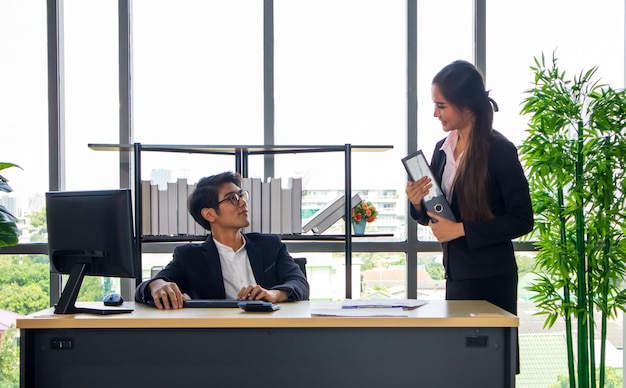 Ein junger asiatischer geschäftsmann und eine sekretärin im büro arbeiten sie gemeinsam bis zur fertigstellung