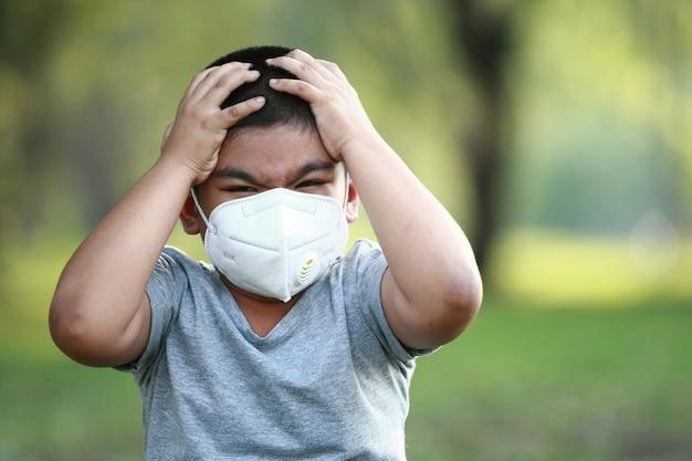 Ein junger asiatischer junge, 7 jahre alt, trägt eine maske zum schutz vor staub pm 2.5 und keimen