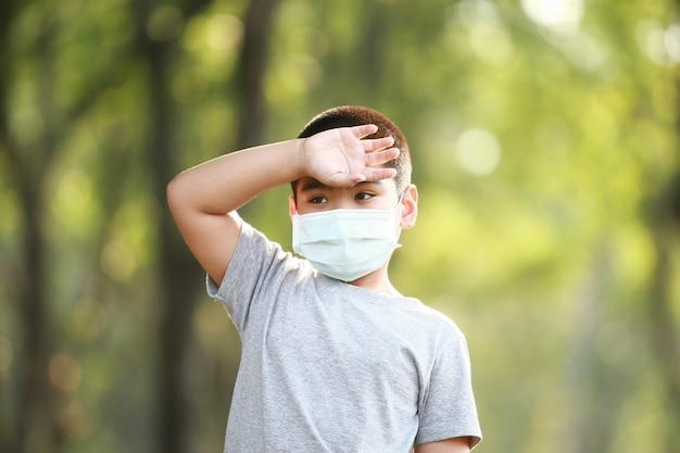 Ein junger asiatischer junge trägt eine maske zum schutz vor staub pm 2.5 und keimen