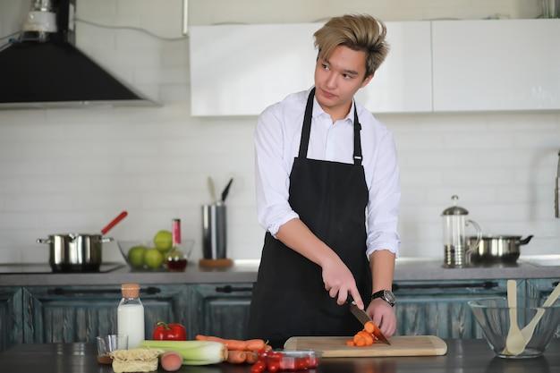 Ein junger asiatischer koch in der küche bereitet essen in einem kochanzug zu