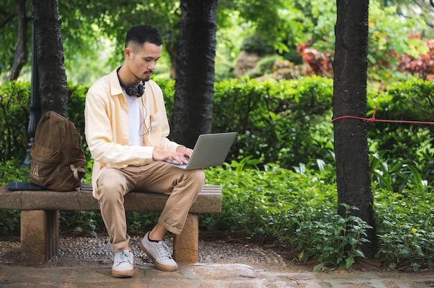 Ein junger asiatischer mann, der sich entspannt und entspannt, indem er musik mit kopfhörer im park hört. gutes gefühl für den sonnigen tag im garten in der urlaubszeit.