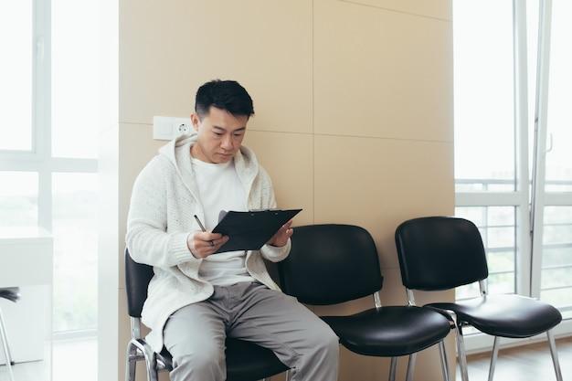 Ein junger asiatischer mann im wartezimmer für ein interview oder ein treffen, das papier hält, während er am stuhl sitzt, füllt einen lebenslauffragebogen im büro aus