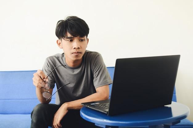 Ein junger asiatischer mann sitzt auf dem sofa und starrt auf den laptop