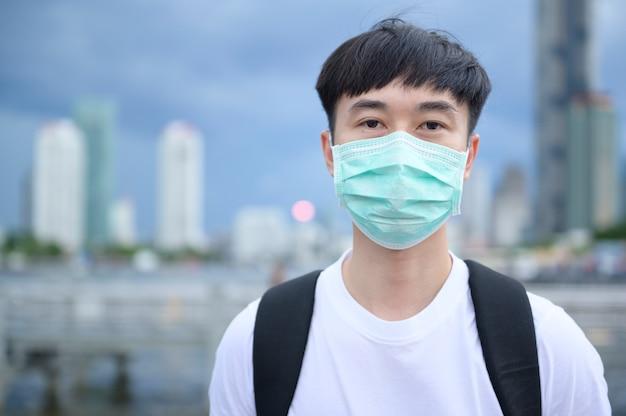 Ein junger asiatischer touristenmann trägt schutzmaske, die draußen steht, coronavirus-schutz, neues normales reisekonzept