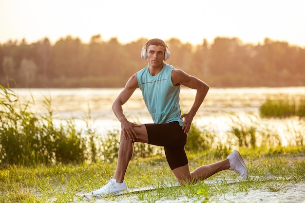 Ein junger athletischer mann, der draußen am flussufer musik hört?