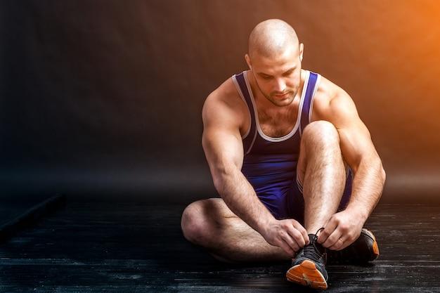 Ein junger athletischer mann in blauem wrestling knifflige und blaue shorts bindet schnürsenkel an turnschuhen auf schwarzem, isoliertem hintergrund in einem fotostudio?
