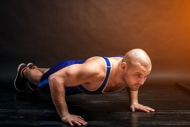 Ein junger athletischer mann in blauen wrestling-trick- und blauen shorts macht liegestütze auf einem schwarzhaarigen, isolierten hintergrund in einem fotostudio