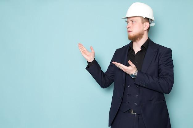 Ein junger attraktiver mann der vorderansicht mit bart im schwarzen dunklen klassischen modernen anzug auf dem blauen raum