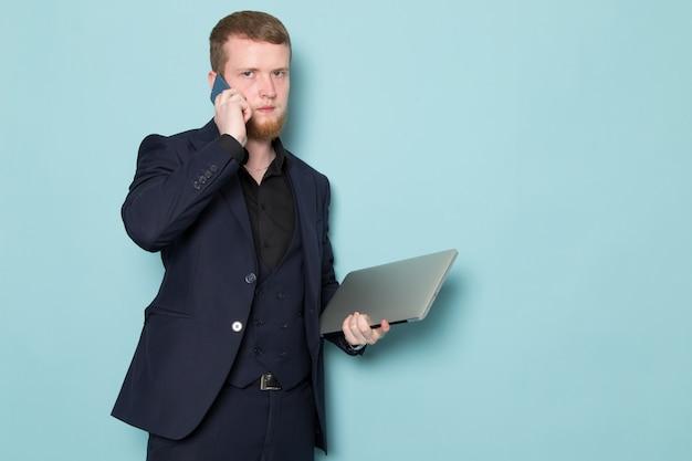 Ein junger attraktiver mann der vorderansicht mit bart im schwarzen dunklen klassischen modernen anzug, der grauen laptop hält, der am telefon auf dem blauen raum spricht