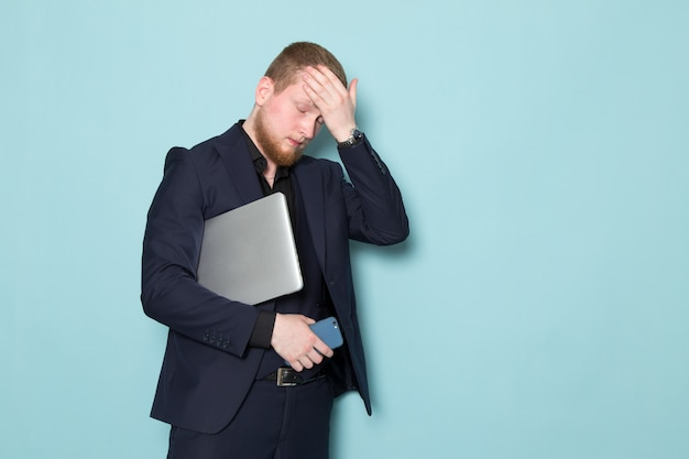 Ein junger attraktiver mann der vorderansicht mit bart im schwarzen dunklen klassischen modernen anzug, der graues laptop-telefon auf dem blauen raum hält