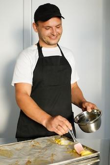 Ein junger bäcker schmiert den teig vor dem backen ein