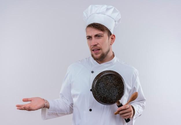 Ein junger bärtiger kochmann, der weiße kochuniform und hut hält bratpfanne mit holzlöffel trägt, während mit aggressivem ausdruck auf einer weißen wand schaut