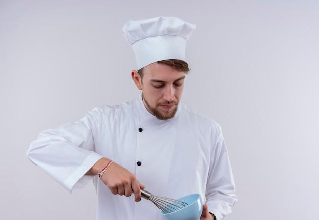 Ein junger bärtiger kochmann, der weiße kochuniform und hut hält mischerlöffel auf blauer schüssel auf einer weißen wand