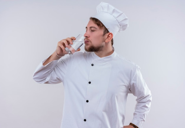 Ein junger bärtiger kochmann, der weiße kochuniform und hut trägt, trinkt ein glas wasser, während er auf eine weiße wand schaut