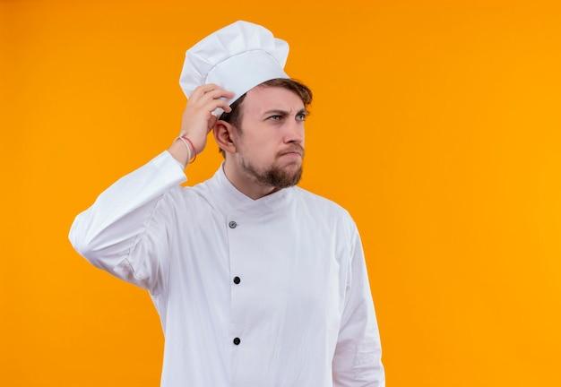 Ein junger bärtiger kochmann in der weißen uniform denkt und hält hände auf seinem kopf, während er auf eine orange wand schaut