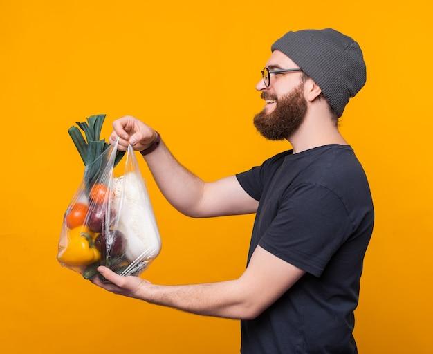 Ein junger bärtiger mann hält einen beutel mit einigen lebensmitteln darin und ein lächeln verschenkt sie