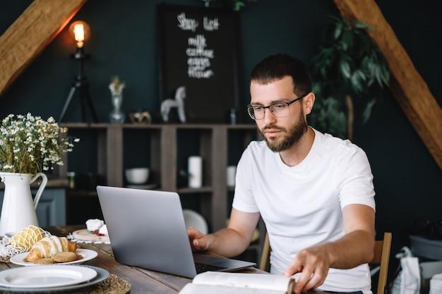 Ein junger bärtiger mann mit brille arbeitet an einem laptop, surft im internet und sucht nach informationen in einem buch