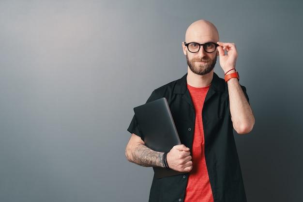 Ein junger bärtiger mann mit brille, die laptop unter dem arm im studio auf grau hält