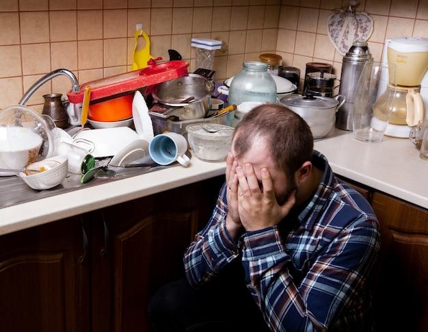 Ein junger bärtiger mann sitzt auf dem boden und ist schockiert über die menge an schmutzigem geschirr, das in der spüle liegt, um gewaschen zu werden.