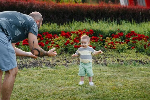 Ein junger bärtiger vater hilft und bringt seinem kleinen sohn bei, seine ersten schritte während des sonnenuntergangs im park auf dem gras zu machen.