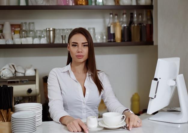 Ein junger barista an der bar serviert kaffee auf einem tablett