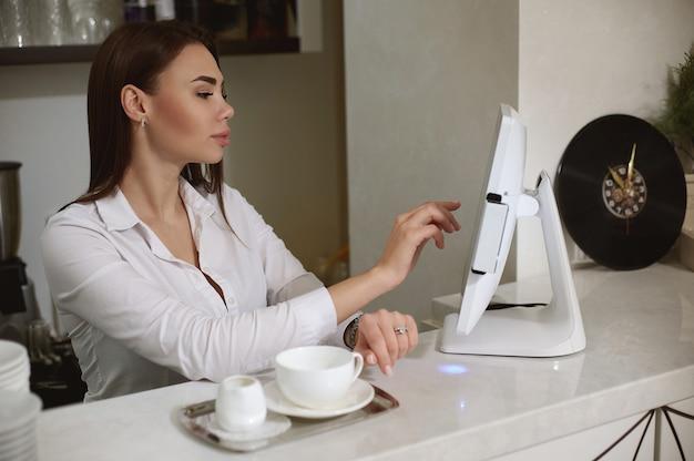 Ein junger barista in weißer uniform druckt die bestellung auf dem monitor