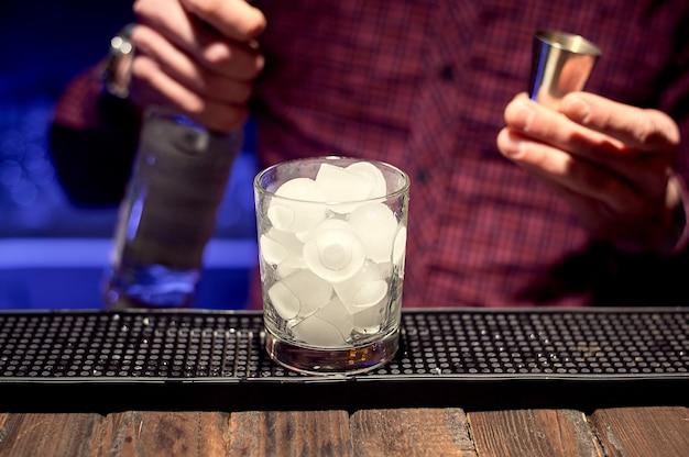 Ein junger barkeeper bereitet in einem nachtclub einen alkoholischen cocktail in einem glas mit eis zu.