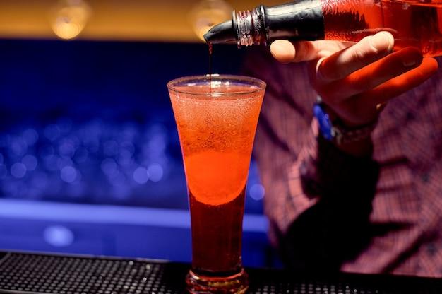 Ein junger barkeeper in einem nachtclub macht einen cocktail mit rotem schnaps.