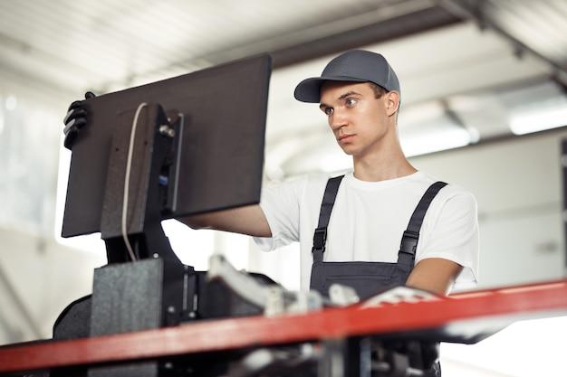 Ein junger blauäugiger mechaniker überprüft mit einem computer ein auto bei einer autowerkstatt.