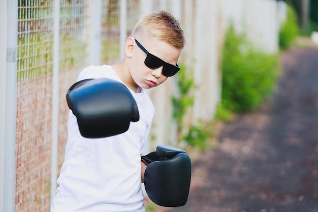 Ein junger blonder junge in einem weißen t-shirt und einer sonnenbrille schlägt mit einer hand in einem boxhandschuh. foto in hoher qualität