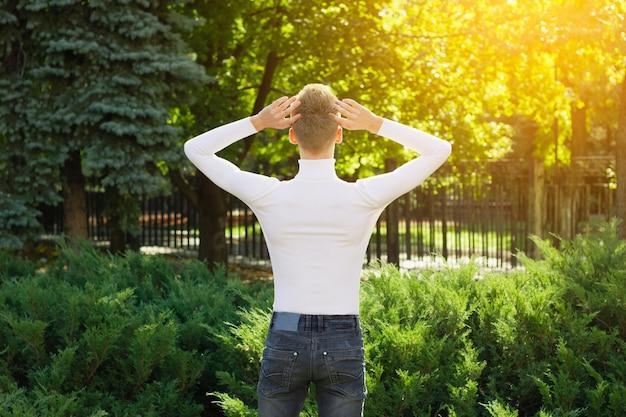 Ein junger blonder mann in einem weißen pullover und schwarzen jeans steht mit dem rücken zur kamera und hält den kopf in den händen vor dem hintergrund eines stadtparks. fotokonzept.