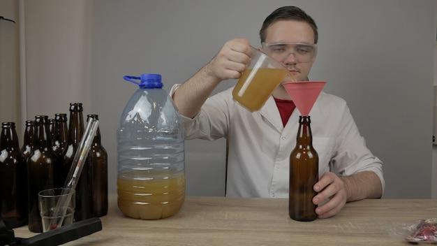 Ein junger brauer bereitet produkte zu und überprüft die qualität der ausrüstung und die qualität des zu hause gebrauten honigbiers
