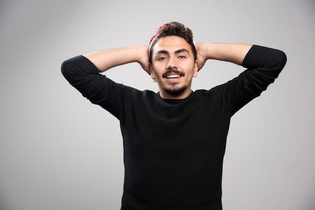 Ein junger brünetter mann, der seine ohren bedeckt und posiert.