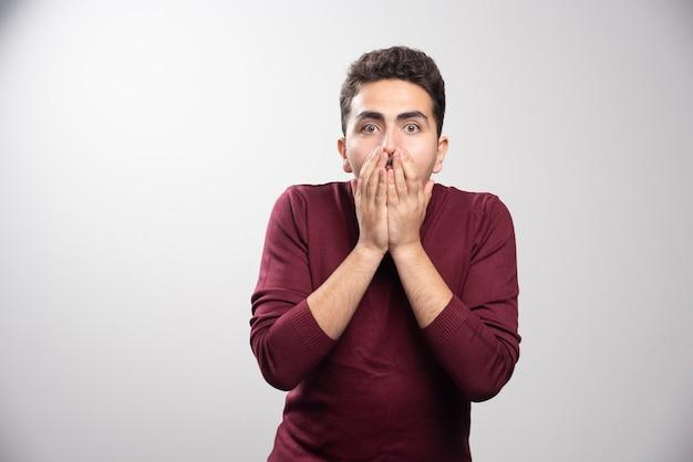 Ein junger brünetter mann, der seinen mund bedeckt und posiert.