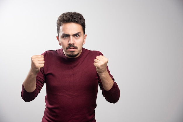 Ein junger brünetter mann, der steht und bereit ist zu schlagen.