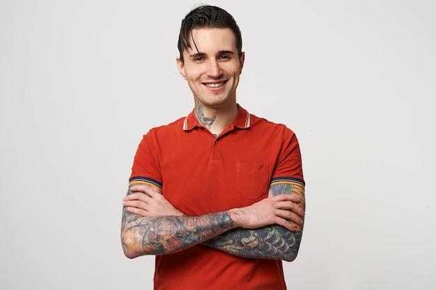 Ein junger brünetter mann mit gefalteten haaren und einem glücklichen lächeln