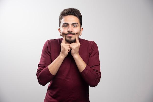 Ein junger brünetter mann verstärkt das lächeln auf einer grauen wand. hochwertiges foto