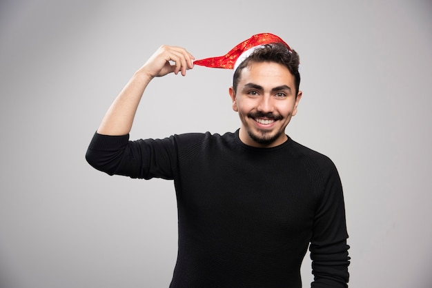 Ein junger brünetter mann zeigt den hut seines weihnachtsmanns und posiert