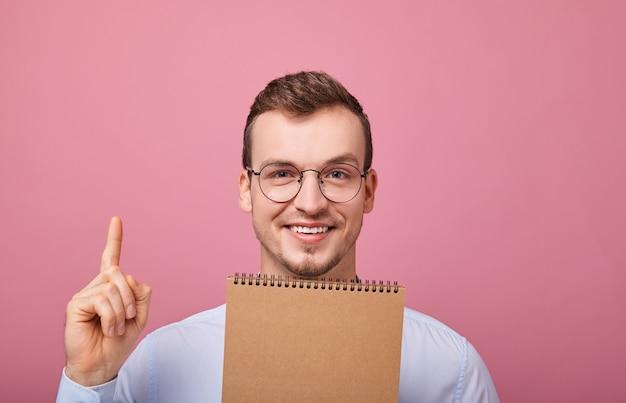 Ein junger cooler typ in einem sanft blauen hemd mit brille taucht auf