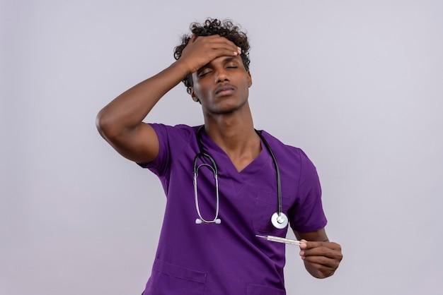 Ein junger dunkelhäutiger arzt mit lockigem haar in violetter uniform mit stethoskop, das das thermometer hält, während er die handfläche auf der stirn hält