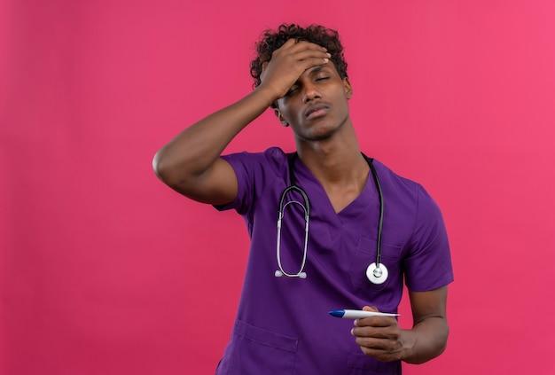 Ein junger dunkelhäutiger arzt mit lockigem haar in violetter uniform mit stethoskop hält die handfläche auf der stirn, während er das thermometer hält