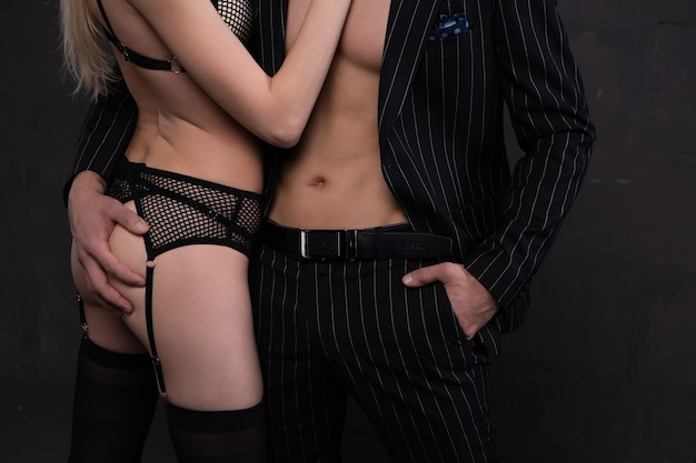 Ein junger eleganter mann umarmt leidenschaftlich ein blondes mädchen in unterwäsche